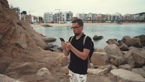 Man på en kust med en smartphone stock video