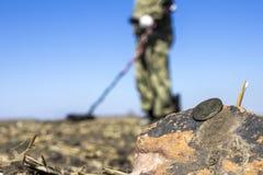 Man på en skattjakt med en metalldetektor i träna på fältet arkivfoto