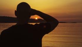 Man på en solnedgångkontur Arkivbild