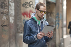 Man på gataavläsningsnyheterna på Tabletdatoren Arkivbild