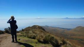 Man på hans baksida som tar foto från Rucuen Pichincha till staden av Quito med den Antisana vulkan i bakgrunden Arkivfoton