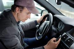 Man på hjulet genom att använda cellmobiltelefonen, medan köra bilen Royaltyfria Bilder