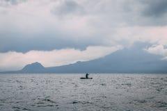 Man på kajaken på sjön framme av berget arkivbild