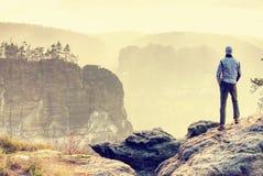 Man på kanten av klippan som är hög ovanför den dimmiga dalen Loppfotvandra och livsstil arkivfoton