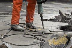 Man på konstruktionsplatsen som demolerar asfalt royaltyfria foton