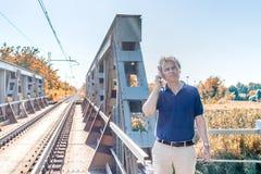 Man på mobila near järnvägspår Royaltyfri Bild