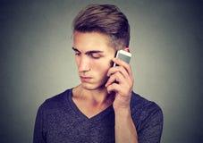 Man på mobiltelefonen med huvudvärk Uppriven olycklig grabb som talar på telefonen arkivbild
