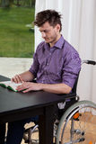 Man på rullstolen som läser en bok Royaltyfri Fotografi