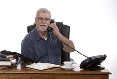 Man på skrivbordet på telefonen Arkivfoto