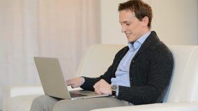 Man på Sofa With en bärbar dator