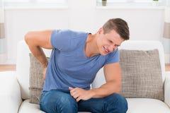 Man på Sofa Suffering From Backpain Arkivfoto