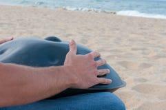 Man på spela för sandstrand som är handpan, eller hängning med havet på bakgrund Hängningen är den traditionella etniska valsmusi royaltyfri foto