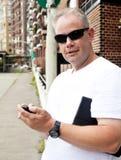 Man på stadsgatan med mobiltelefonen Arkivbilder