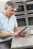 Man på Tabletdatoren i dricka kaffe för kök Arkivbild