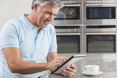 Man på Tabletdatoren i dricka kaffe för kök Royaltyfri Bild