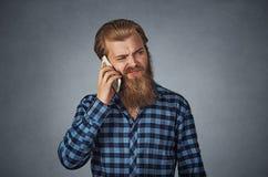 Man på telefonen med cell- mobilt utstrålningsbegrepp för huvudvärk royaltyfria foton