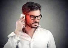 Man på telefonen med huvudvärk Uppriven olycklig grabb som talar på en mobiltelefon royaltyfria foton