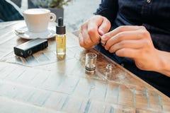 Man påfyllning av av en elektronisk cigarett eller sprejflaska med e-flytande Royaltyfria Bilder