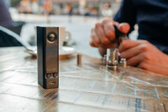 Man påfyllning av av en elektronisk cigarett eller sprejflaska med e-flytande Royaltyfri Bild