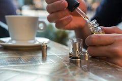 Man påfyllning av av en elektronisk cigarett eller sprejflaska med e-flytande Royaltyfri Foto