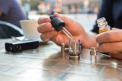 Man påfyllning av av en elektronisk cigarett eller sprejflaska med e-flytande Arkivfoton
