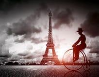 Man på den retro cykeln bredvid det Effel tornet, Paris, Frankrike Arkivfoton