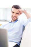 Man på soffan med bärbara datorn Fotografering för Bildbyråer