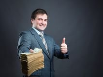Man with pack of money  isolated on gray. Happy businessman holding big pack of money Stock Photos