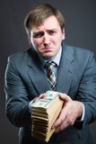Man with pack of money  isolated on gray. Sad man holding big pack of money Royalty Free Stock Photo