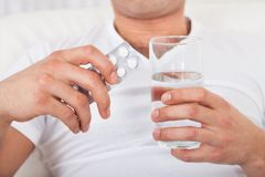 Man With Pack Of Pills And Water Glass Stock Photography