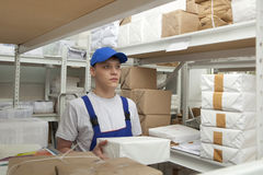 Man with package  in uniform at warehouse Stock Photos