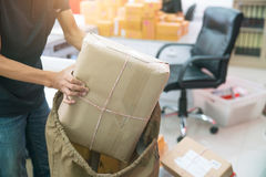 Man is packing into the bag for delivery. Stock Images