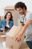 Man Packing Box With Sellotape. Young Man Packing Cardboard Box With Woman In Background Royalty Free Stock Images