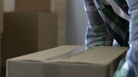 Man packing cardboard box with adhesive tape, moving out, migration, life change. Stock footage stock video