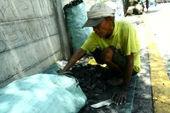 Man packing charcoal into a sack Stock Photos