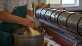 Man packing cheese ready for processing. Man packing cheese into a metal container ready for processing Royalty Free Stock Photo