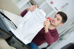 Man packing clothes into travel bag Stock Images