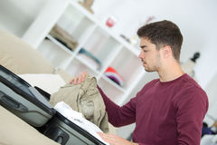 Man packing clothes into travel bag Stock Image