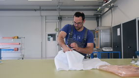 Man packing product on table in factory stock video footage