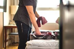 Man packing suitcase for vacation. Person putting clothes to bag. Gagge in hotel room or home bedroom. Traveler with open luggage on bed. Holding t-shirt in hand Stock Images