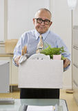 Man Packing up Belongings. An elderly man is in an office and is holding a box of personal belongings. He is looking at the camera.  Vertically framed shot Royalty Free Stock Images