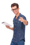 Man with pad points at you. Casual young man with a pad in his hand, pointing and smiling at the camera. isolated on a white background Stock Photo