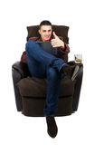 Man with pad, whiskey and thumb up. Business man with pad, whiskey and thumb up sitting on the couch. White background Stock Photo