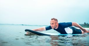 Man padding to line up on the surf board.  Active holidays spending concept stock photography