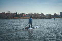 Man on paddle Board on the background of the city, sail on the sup boards in the river city. Man on paddle Board on the background of the city stock photo