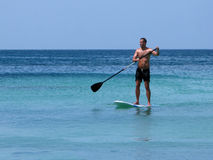 Surfing. Man on paddle board. Tanned man stands up on paddle board with oar in sea. Seawater with different shades of blue Stock Image