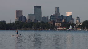 Man Paddle-boarding on Lake Calhoun with Minneapolis Skyline in Background stock video footage