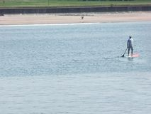 A man paddle boarding at Portrush harbour Co. Antrim Northern Ireland. Space for text copy royalty free stock photo