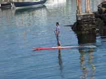 A man paddle boarding at Portrush harbour Co. Antrim Northern Ireland. Space for text copy stock photo