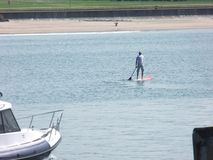 A man paddle boarding at Portrush harbour Co. Antrim Northern Ireland. Space for text copy royalty free stock image
